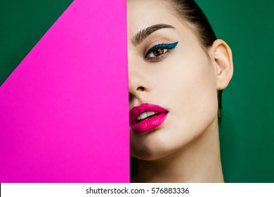 closeup  beauty portrait of young woman with bright makeup on colored background