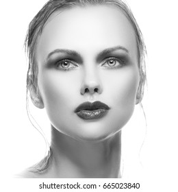 Close-up beauty woman face wiih clean skin and bright make-up over white background. Black and white