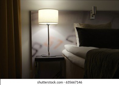Closeup of a bed and bedside table with a lamp standing on it