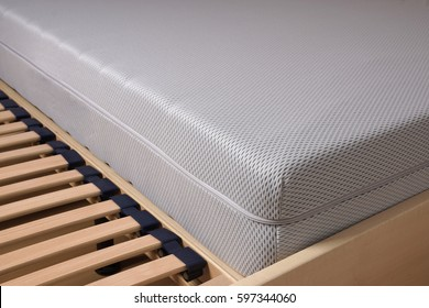close-up of bed with cold foam mattress on slatted frame