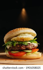 Close-up of beef burger with poached egg. Hamburger - bun, grilled meat burger,arugula salad, tomato and fried egg.