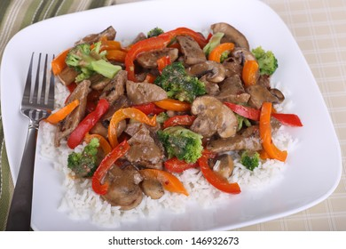 Closeup of beef stir fry dinner mixed with broccoli, mushrooms and peppers on top of rice