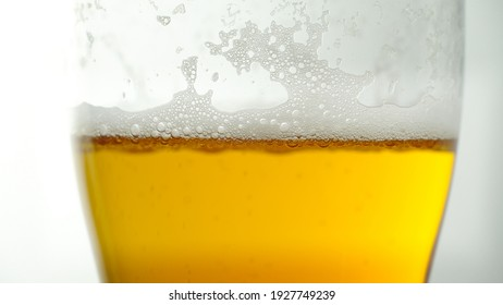 Close-up of beer bubbles with foam in a glass glass . Light beer on a white background.