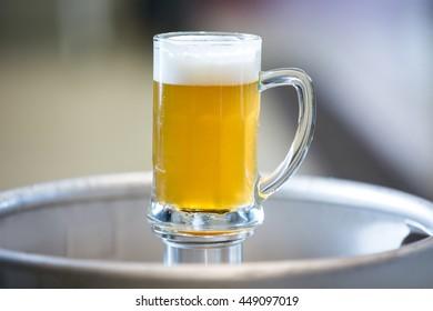 Close-up of beer pint on keg at bewery