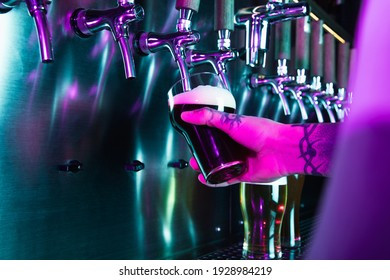 Close-up beer pumps taps in pub or bar in multicolored neon light.