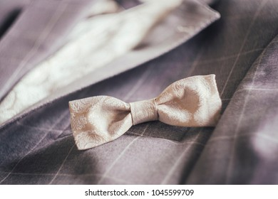 Closeup with a beige bow-tie, and a suit on the background.