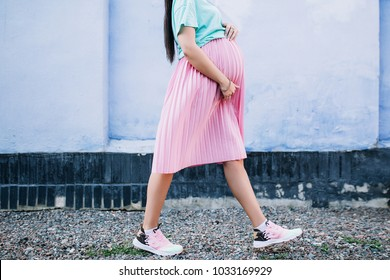 close-up of the belly and legs of a pregnant stylish girl in a pink skirt and mint shirt that goes against a blue wall background