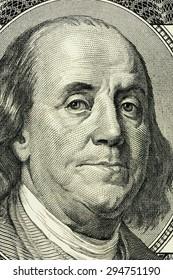 closeup Benjamin Franklin face on the US $100 dollar bill.