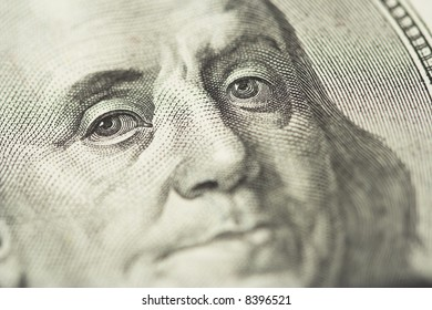 Close-up of Benjamin Franklin, one hundred dollars note. Shallow dof, focus on eyes.
