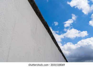 Close-up of the Berlin Wall (German: Berliner Mauer), the most famous part of the entire border installation. 4m high concrete slab wall with pipe top. View into the blue sky with clouds. Sunny day.