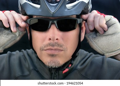 Close-up of bicycle courier putting on his sunglasses.