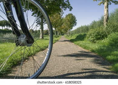 Close-up of a bicycle wheel on a path in nature on a sunny day