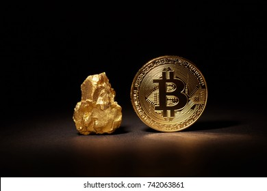 Closeup of big gold nugget and Gold Bitcoin Coin on black background. Bitcoin cryptocurrency. Business concept.