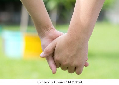 Closeup big kid hand in hand with small child, playing in playground. Children holding hand together in park with green grass. Universal Children's Day November 20th.