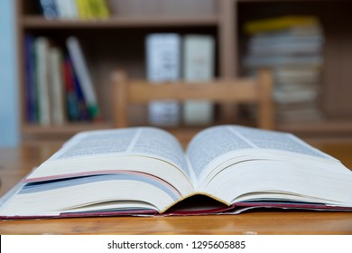 A closeup of a big opened book on a table with bookshelves as background