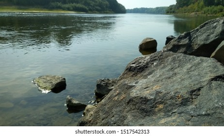 Close-up of big rock near the river. Rock formation near the river against the background of the forest.