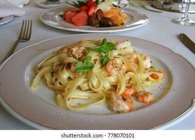 Close-up of Big shrimp pasta dish with a fruit salad dessert