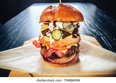 Closeup of big tasty grilled beef burger with lettuce and mayonnaise served on pieces of brown paper on a rustic wooden table