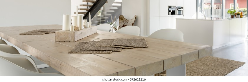 Close-up of big wooden family table in contemporary dining hall