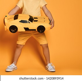 Closeup. Big yellow toy race car in kid boy hands standing on yellow background with free text space