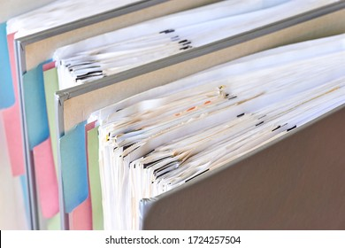 Closeup of binders with papers and tabs. Stack of business papers, bills or documents in standing document binders. Debt free life, business office stress workload or paperless office concept.