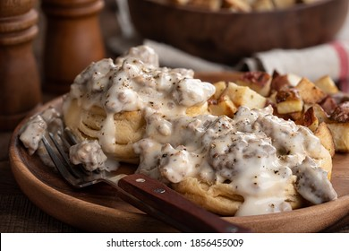 Closeup of biscuits with creamy sausage gravy and fried potatoes on a wooden plate