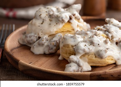 Closeup of biscuits and creamy sausage gravy on a wooden plate