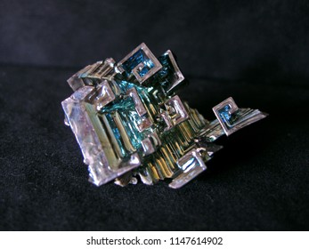 Closeup of a bismuth crystal on black fabric with metallic reflexes of blue and pink
