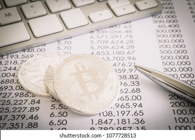 Closeup bitcoins cryptocurrency on transaction paper reports with silver pen and keyboard. Electronic digital money transfer through blockchain, decentralized cyber network, proof of work concepts.