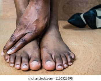 Closeup of black African woman bare foot suffering from painful toes. Removed her  stilettos in discomfort at work, shoe store or home for High heels shoe feet pain and foot problem concept