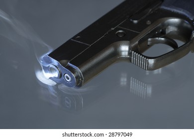 Close-up of black automatic pistol with smoke near barrel's hole