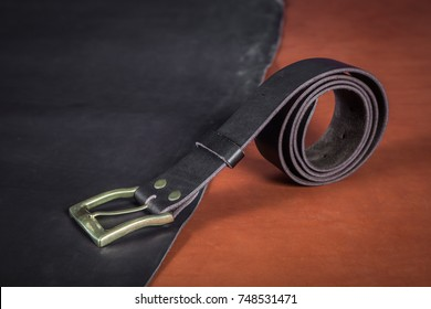 A close-up black belt made of genuine leather made by hand and a few buckles lie on the table on pieces of black and brown leather