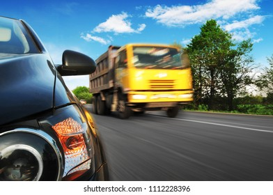 Close-up of a black car front with a headlight and mirror on a countryside road in a motion with a yellow truck driving fast against blue sky with clouds