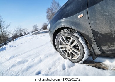 Close-up of a black car on a winter countryside road with snow against a blue sky