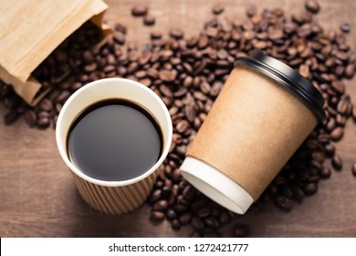 Closeup black coffee in paper cup and coffee beans spilled out the paper bag