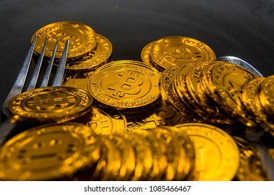 Close-up Black food plate, with fork and golden bitcoin on black background, abstract business concept of modern business, comparable bitcoin