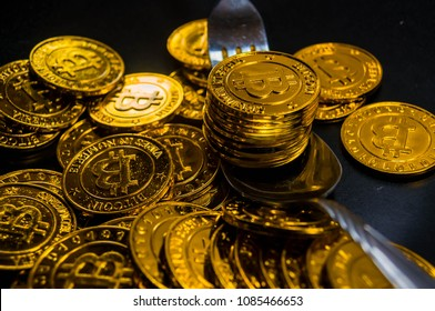 Close-up Black food plate, with fork and spoon, and golden bitcoin on black background, abstract business concept of modern business, comparable bitcoin