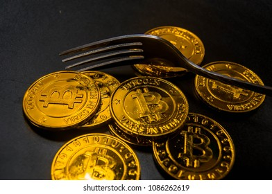 Close-up Black food plate, with fork and golden bitcoin on black background, abstract business concept of modern business, comparable bitcoin, like food to eat.