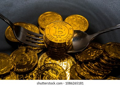 Close-up Black food plate, with fork and spoon, and golden bitcoin on black background, abstract business concept of modern business, comparable bitcoin, like food to eat.