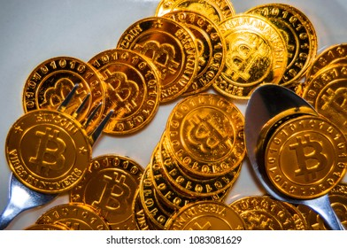Close-up Black food plate, with spoon and golden bitcoin on white background, abstract business concept of modern business, comparable bitcoin, like food to eat.
