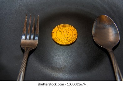 Close-up Black food plate, with spoon and golden bitcoin on black background, abstract business concept of modern business, comparable bitcoin, like food to eat.