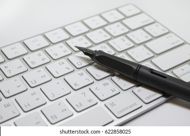 Closeup of black fountain pen on white computer thai-eng keyboard