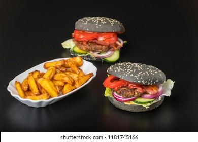 closeup of black hamburgers on black slate