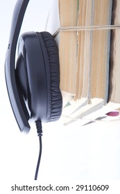 Close-up of black headphones and wire with the pile of books. Isolated on a white background.