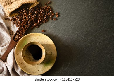 Close-up of Black hot coffee with milk foam in black ceramic cup and napkin with coffee beans roasted in a sack on dark stone table background. Top view, flat lay with copy space for your text.
