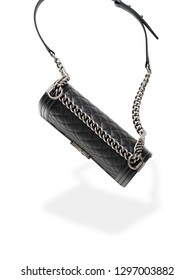 Close-up of black leather handbag on white background. Steel chain and leather belt. Luxury accessory