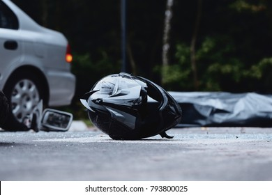 Close-up of black motorcycle helmet. Inattentive car driver on the road with motorcyclist