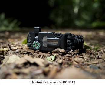 Closeup Black multifunction paracord survival bracelet for camping on forest floor, with whistle, compass, flint striker. 1 of 2