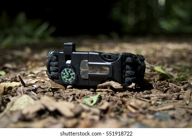 Closeup Black multifunction paracord survival bracelet for camping on forest floor, with whistle, compass, flint striker. 2 of 2