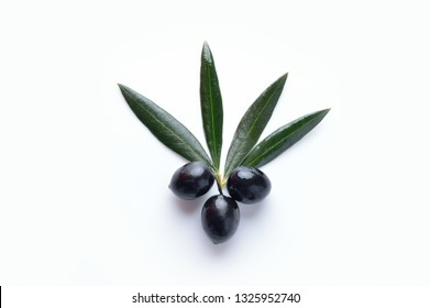 Closeup of black olives with olive branch on white background